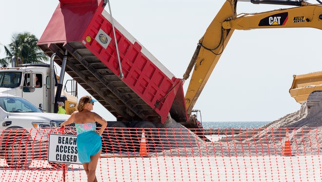 Dump trucks deliver sand from an inland mine to South Beach on Marco Island during a Collier County beach renourishment project on Nov. 2, 2016.