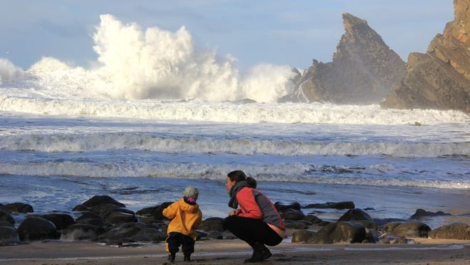 Lucy Urness and Robyn Orr watch a wave crash near Sunset Bay State Park.