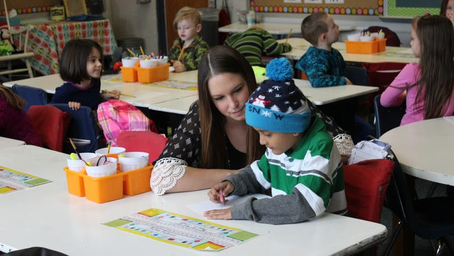 JackelynHoltz helps a student during their spelling test.