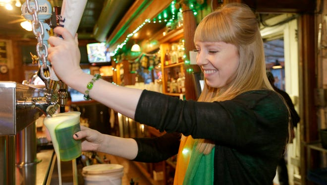 Amanda Mickevicius, a bartender at O'Lydia Bar and Grill in Milwaukee, serves up a green beer on St. Patrick's Day.