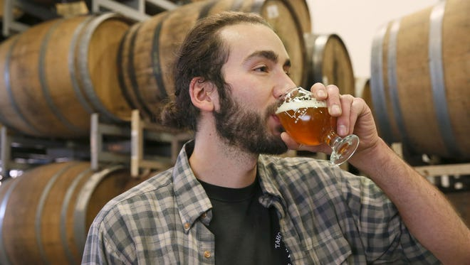 Brewer Adam Thomas samples a sour beer at MobCraft, 505 S. 5th St. Behind him, beer ages in barrels for flavor.