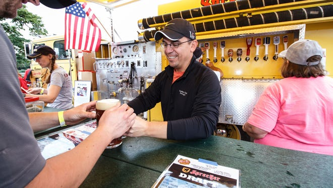Waukesha Kiwanis member Miguel Ocampo serves up a stein of beer at Oktoberfest in Waukesha's Frame Park on Sept. 24, 2016. This year's Oktoberfest is scheduled for Sept. 22-23.