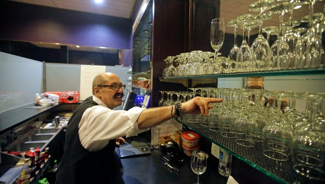 A server from Lamb's Grill reaches for a glass while preparing drinks at the Salt Lake City restaurant. Gov. Gary Herbert is planning to sign a new law toughening drunken-driving restrictions that restaurateurs worry could prompt fewer people to eat out.