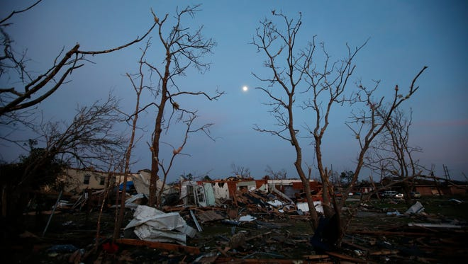 FILE - In this Feb. 8, 2017 file photo, the moon rises over a destroyed neighborhood in the aftermath of a tornado that tore through the New Orleans East section of New Orleans.  Forecasters are warning of severe storms as a powerful system moves across the central United States, the start of what could a turbulent stretch of spring weather over the next few days. The bull's-eye for some of the most fearsome weather _ including possible tornadoes, s over parts of Louisiana, Arkansas and east Texas on Friday, March 24 forecasters said.