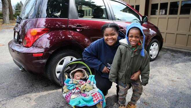 Marticia Jenkins and her children, Logan, 4, and Olivianna, nearly 1 year, happily pose with the car purchased for them with money raised in a GoFundMe campaign online.