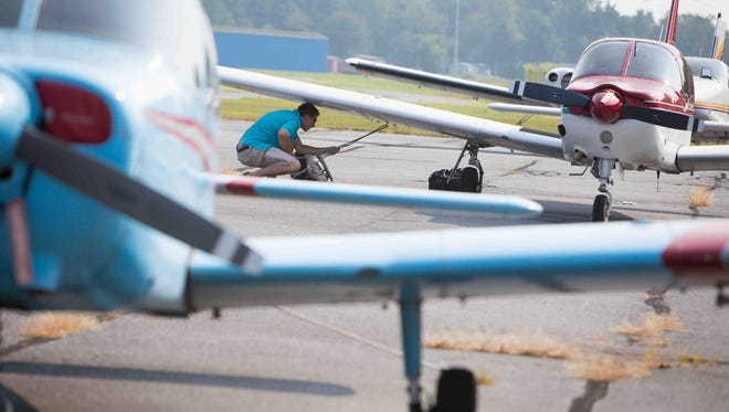 Delaware State University junior Paul Sherry secures a plane after completing a flight at Delaware Airpark in Dover