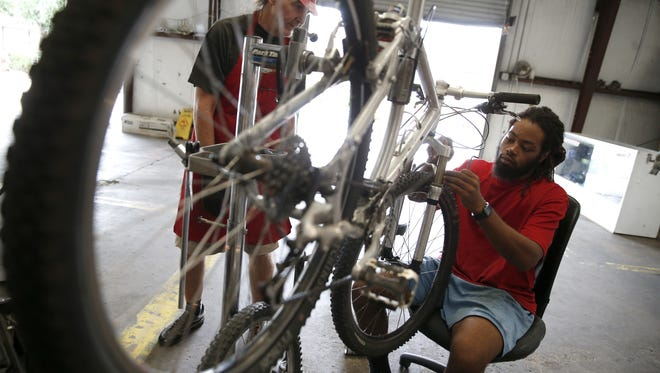 Head Mechanic Neely Williams, right, and long-time volunteer Kevin Carroll work on adjusting a bike's front brake at the Bicycle House Wednesday, where the non-profit uses spare parts donated by local police departments to repair and create bicycles in exchange for a request of nominal donations.