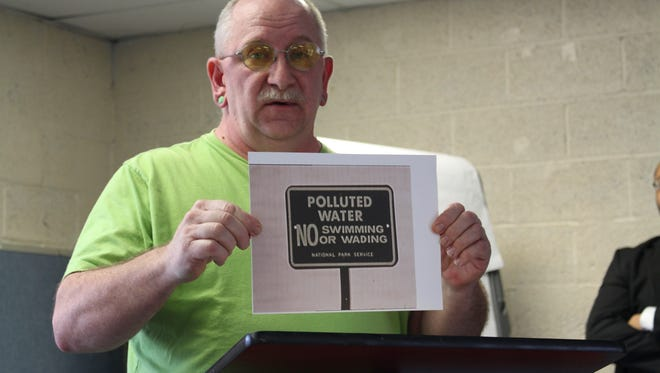 Local environmental activist Bill Baker holds up a picture of a sign about polluted water at a press conference at NECIC on Tuesday, March 28, 2017. Baker said he can remember seeing the National Park Service signs when he was growing up in the 1970s in Mansfield.