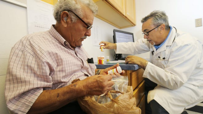 La Fe Clinic patient Jose Sotelo, left, and Dr. Juan Loya, La Fe medical director, review Sotelo's medications during an office visit Tuesday.