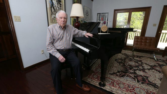 Opera composer Carlisle Floyd sits at his piano at his home in Tallahassee. The National Medal of Arts hangs in a display by his left hand. His niece is encouraging him to write a Christmas opera.