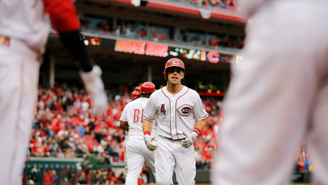 Cincinnati Reds second baseman Scooter Gennett (4) heads back to the dugout after hitting a two-run home run in the top of the ninth inning of the MLB Opening Day game between the Cincinnati Reds and the Philadelphia Phillies at Great American Ball Park in downtown Cincinnati on Monday, April 3, 2017. The Reds lost the season-opening game to the Phillies, 4-3.