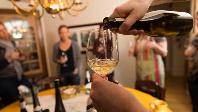 A glass of Riesling is poured at a wine club gathering at the home of Erin Grace in Milwaukee. The topic of this meeting was wines from Austria.