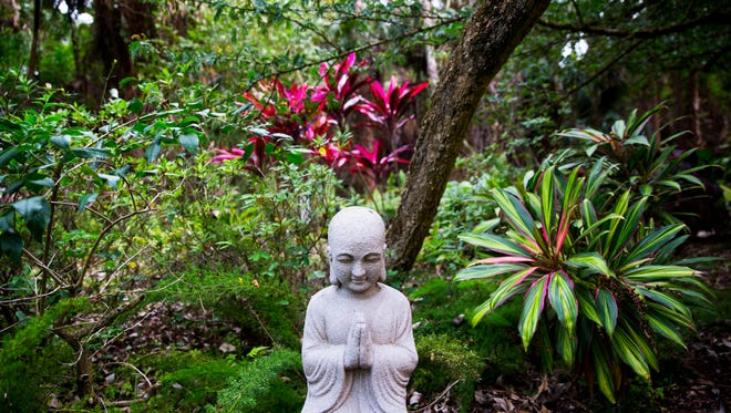 A praying Buddha statue sits among plants in Annette Mazzeo-Eskin's Japanese-inspired zen garden at her Golden Gate Estates home on Tuesday, April 11, 2017.