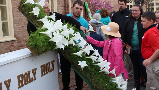 A girl receives a lily from a cross of greenery during St. Mark's Lutheran Church's 60th Annual Easter Sunrise Service on Sunday, April 16, 2017. The service was held at Kingwood Center Gardens.