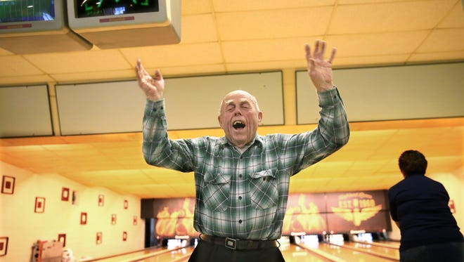 Chet Worzala, who turned 90 this bowling season, celebrates a strike during league bowling at Highland Lanes in Milwaukee. His team also includes his wife, Mary, and daughter, Joanne Mauser.