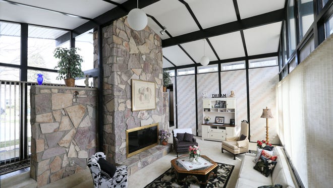 The living room has a stone fireplace and furnishings the original homeowners left for them. Almost all of the exterior walls in the home are covered with custom vertical blinds.