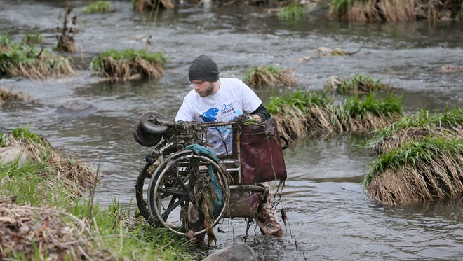 Chris Wiegand, of Milwaukee, lifts a wheelchair out of Lincoln Creek Thursday. Wiegand was among 30 volunteers removing trash from the stream Thursday.