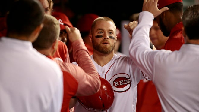 Tucker Barnhart celebrates as he returns to the dugout after scoring in the MLB National League game between the Cincinnati Reds and the Chicago Cubs at Great American Ball Park in downtown Cincinnati, on Friday, April 21, 2017. The Cubs tied the game with a 3-run top of the ninth and went on to beat the Reds 6-5 in 11 innings.