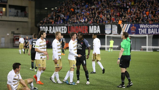 FC Cincinnati's Djiby Fall, right, is issued a red card and gets into an altercation with Louisville City's Niall McCabe during a match at Nippert Stadium April 22, 2017.