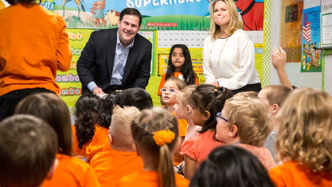 Arizona Gov. Doug Ducey listens to a student during a visit to BASIS Phoenix Central in 2016.
