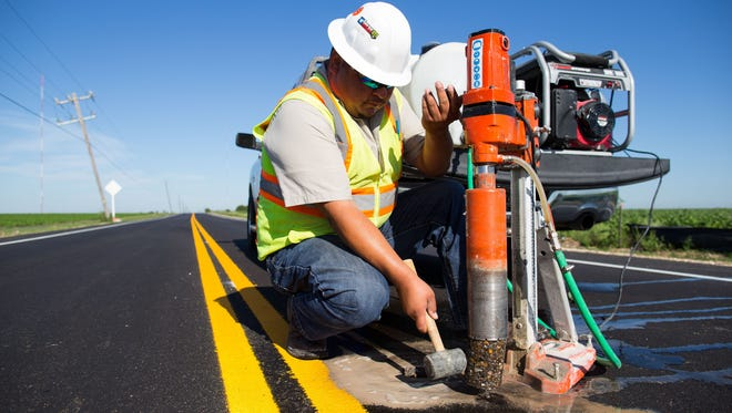 Juan Melgoza, construction material technician for the city of Corpus Christi, hammers out a core sample from the  newly rebuilt County Road 20 on May 6, 2016.