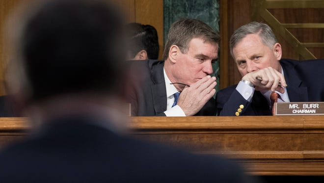 Chairman of the Senate Select Committee on Intelligence Republican Richard Burr (R) and ranking member of the Senate Select Committee on Intelligence Democrat Mark Warner (L) speak with one another while witnesses testify during a recent  hearing.