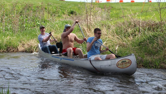The men of Boat 65 - (from left) Luke Nevermann, Andrew Stempel and Ben Bliss - prepare themselves for a sharp jag in the Pewaukee River in the 2014 race.