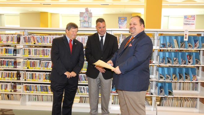 West Florida Public Library Director Todd Humble, right, holds library cards for Escambia County School District students during a presentation with Escambia County School District Superintendent Malcolm Thomas, left, and Escambia County Commissioner Doug Underhill on Monday, May 8, 2017, at the Spring Street Library in Pensacola.