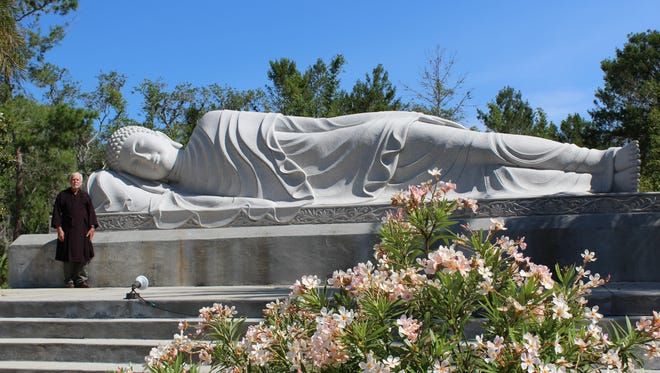 Ron Henderson, a staff member at the White Sands Buddhist Center in Mims, stands next to the Nirvana Buddha statue. The statute is one of three massive monuments currently at the center, and weighs about 40 tons. It's about 30 feet long.