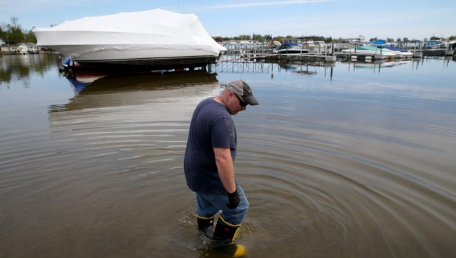 Dave Mills wades into what was the the dry dock at  Arney's Marina in Sodus Point. Many boaters are holding off on getting their boats in because of the flooding and hazards on the lake.