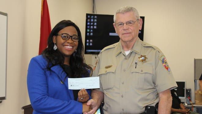 Sheriff Mike Fitzhugh presents a $1,000 SRO scholarship to Stewarts Creek High School senior Asia Johnson.