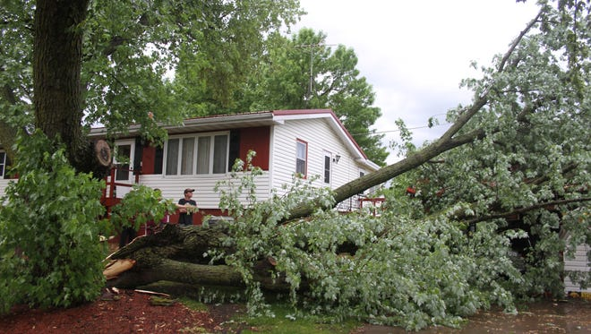 Residents investigate damage this fallen tree caused to a garage along the 600 block of East South Street Wednesday, May 17.