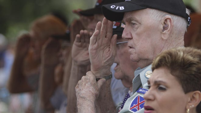 In this 2013 file photo, veteran Dick Sayers salutes during the singing of the National Anthem at a Memorial Day service held at Coral Ridge Funeral Home & Cemetery in Cape Coral.