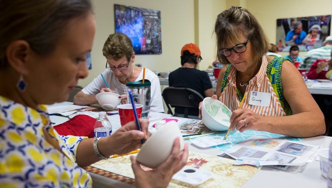 Ginny Bonnough, from right, Micheline Ruiz and Tonya Dubois paint ceramic bowls during an Empty Bowls Naples Inc. public painting event Sunday, May 21, 2017. The painted bowls will be sold and used to serve soup during the 12th annual Empty Bowls Naples event in January.