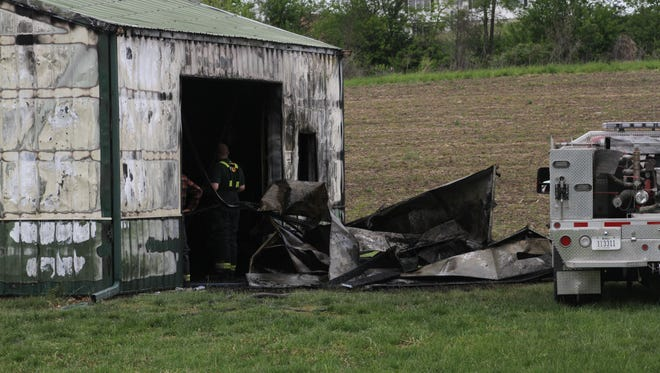 Firefighters investigate the gutted ruins of this barn at a residence near Oxford Tuesday, May 23.