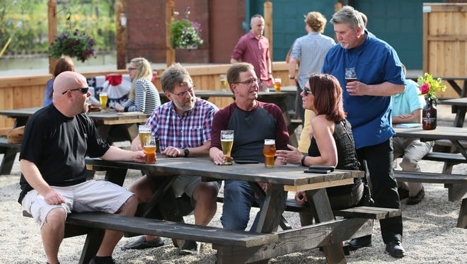 Beer lovers Jay Ranallo of Milwaukee, Jay Stutz of Cedarburg, Rick Jung of Cedarburg, Felicia Jung of Cedarburg and Bill Maca of Grafton enjoy a pint on the patio at City Lights Brewing. The brewery is at 2210 W. Mount Vernon Ave.