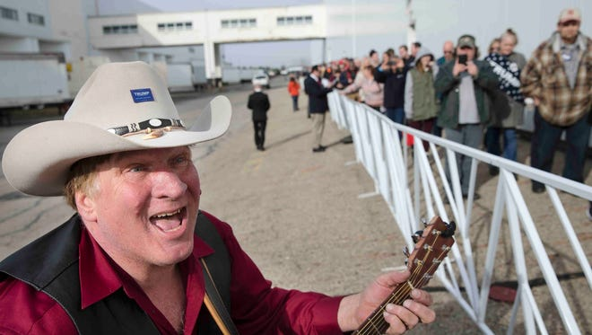 """In this March 1, 2016 file photo, Kraig Moss plays a song for attendees as they wait in line before the arrival of Republican presidential candidate Donald Trump ahead of a campaign stop at the Signature Flight Hangar at Port-Columbus International Airport in Columbus, Ohio. """"He promised me, in honor of my son, that he was going to combat the ongoing heroin epidemic,"""" Moss said of a January 2016 presidential campaign interaction with Trump. Trump's budget proposal released Tuesday, May 23, 2017, weakens insurance coverage for drug addiction treatment and cuts back funding for research and prevention programs."""