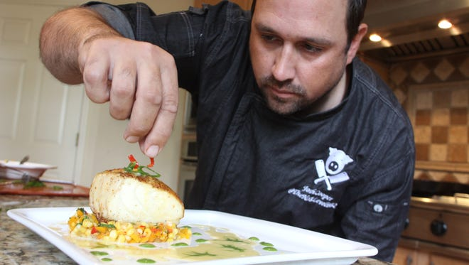 MasterChef contestant Josh Coopers adds the finishing touches to Chilean sea bass over a corn, pepper and cilantro salad.