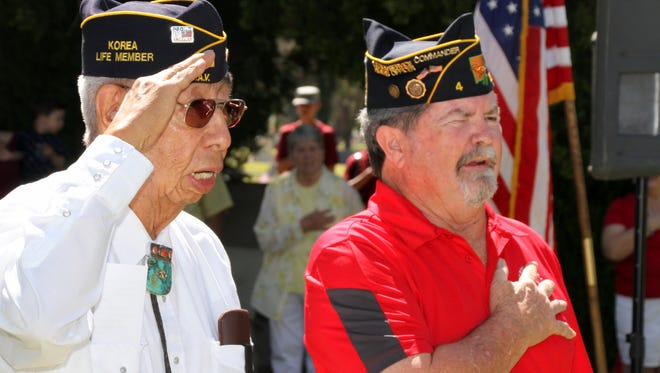"Korean War veteran Ruben Acosta, left, and American Legion Bataan Post 4 Commander Ed Miller lead the audience in the ""Pledge of Allegiance"" during Monday's Memorial Day ceremony at Mountain View Cemetery on Deming's east side."