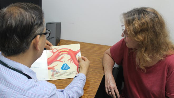 Dr. Ramel Carlos, left, with Susan Ruth Quintanilla in his Tamuning clinic, discussing silent stroke with a diagram of a blood vessel.
