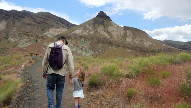 Lucy Urness and Matt Achor hike the overlook trail outside the Thomas Condon Paleontology Center.