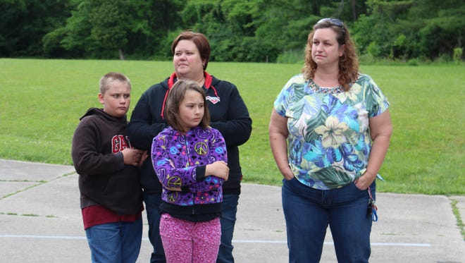 Danell Allen, right, stands with a second Elmwood Drive resident and her two children who asked not to be named during a meeting at North Lake Park on Tuesday, June 6, 2017. The two Elmwood Drive families would be forced out of their homes if the city approves a project to build a dam in the area to prevent flooding.