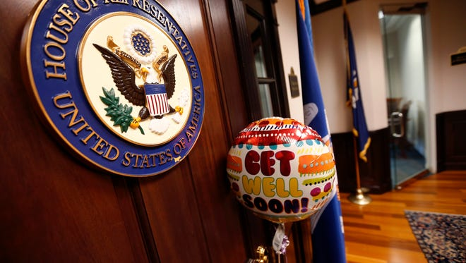 A balloon and card from the office of Sen. Bill Cassidy, R-La., is seen tied to the door of the closed office of Rep. Steve Scalise, R-La., in Metairie, La., Wednesday, June 14, 2017. Scalise was shot while practicing with fellow lawmakers for a congressional baseball game in Alexandria, Va. (AP Photo/Gerald Herbert)