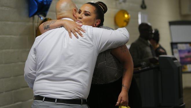 Graduate Kristel Mason hugs staff.