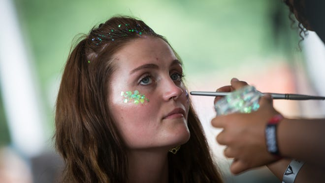 Hannah Bryce, of Pittston, Pa., has her face painted at the Toyota Music Den at Firefly Music Festival Friday.
