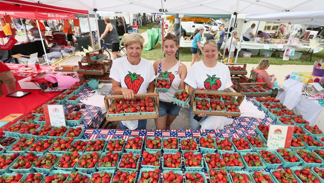 Cheryl Schmit (from left), Clair Paul and Donna Bornitz sell strawberries grown at Schmit Farms in Mequon and East Troy at the 2016 Strawberry Festival in Cedarburg.