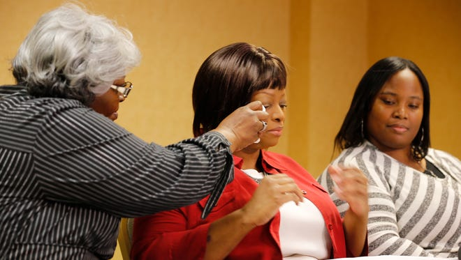 Audrey DuBose, Sam DuBose's mother, dabs away tears from his sister, Terina Allen's, eyes during a Tuesday press conference. Cleshawn DuBose, Sam DuBose's sister sits to the right.