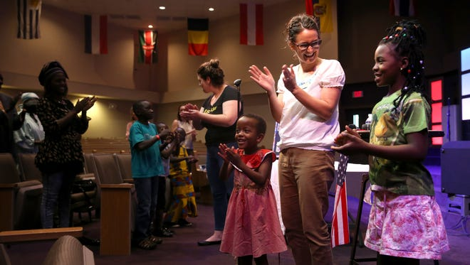 Kim Thacker sings a song and claps along with refugee children Ange Barasora, 5, and Hope Nyiramugisha, 11, during a gathering in honor of last week's World Refugee Day at Freedom Church on Tuesday.