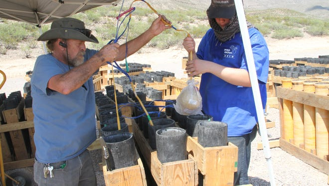 Roy Moore (L) and Alex Thompson load 6-inch fireworks shells into its tubes on Monday in preparation for Alamogordo's fireworks show.