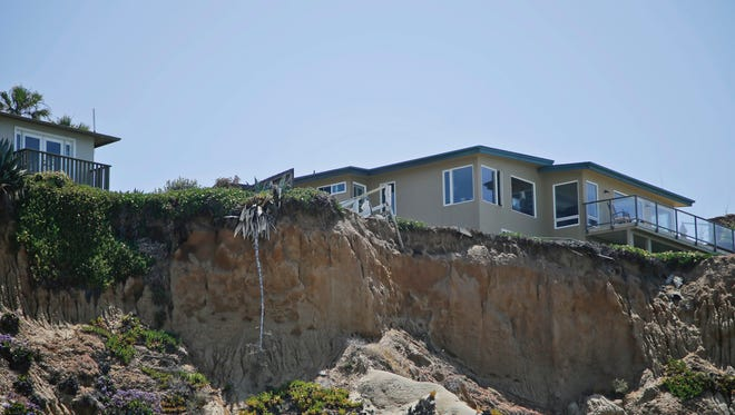 In this May 20, 2013, file photo, one of several homes which have lost their yard hang over the edge of a cliff in Solana Beach. California property owners give up their right to pursue lawsuits challenging restrictions in building permits once they construct the project, the state's high court said.